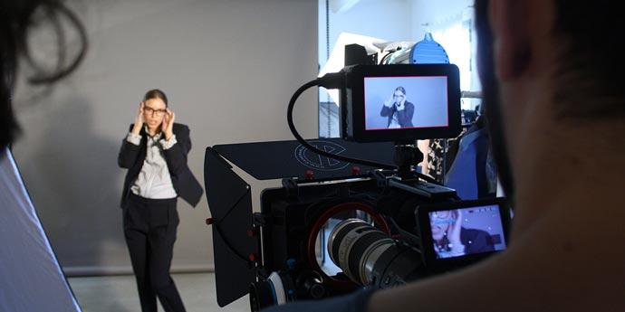 La modella posa davanti alla videocamera di istantanee durante lo shooting organizzato da big rocket
