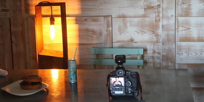 Macchina fotografica e hamburger su tavolo durante pausa shooting fotografico