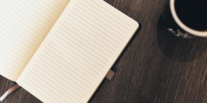 Foglio bianco e penna su scrivania pronti per la scrittura di un romanzo
